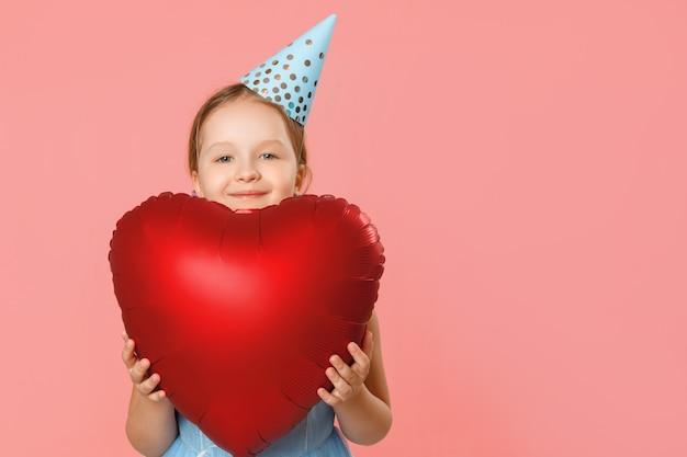 A menina em um tampão prende um balão em forma de coração grande.