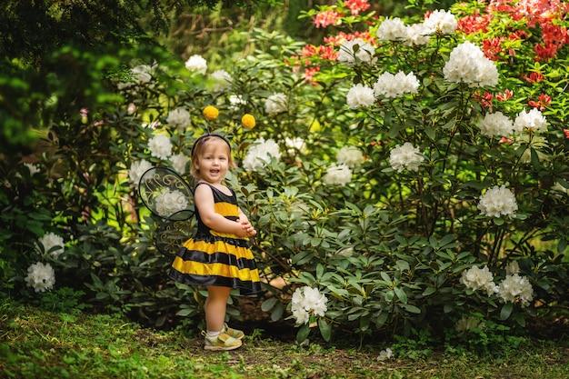 A menina em um terno de uma abelha perto de um arbusto. a criança sonha e é jogada. copie o espaço