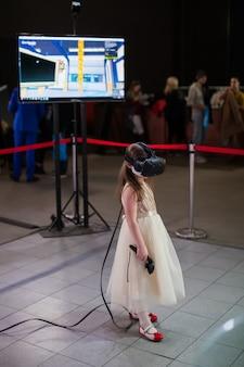 A menina em um vestido bonito e em vidros da realidade virtual em sua cabeça joga o jogo do vr na exposição da tecnologia.