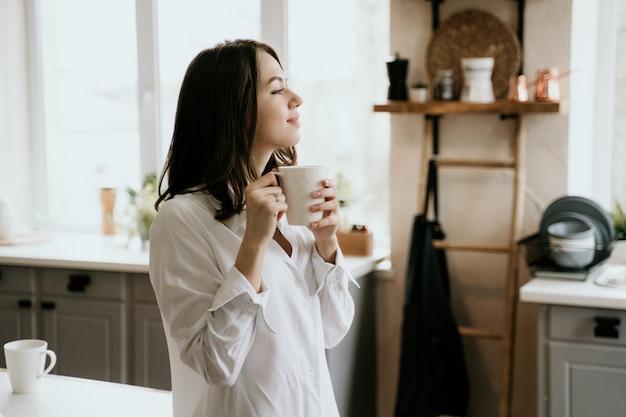 A menina em uma camisa branca bebe o café na manhã em uma cozinha.