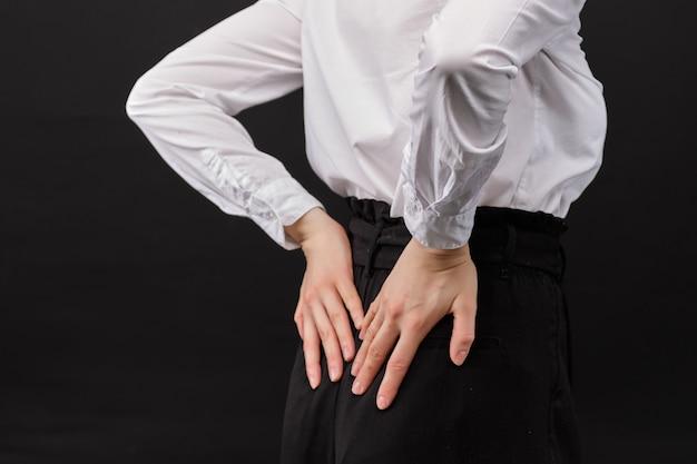 A menina em uma camisa branca massageia a parte inferior das costas em um fundo preto.