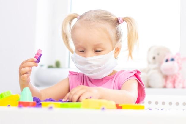 A menina em uma máscara médica protetora joga areia cinética em quarentena. a menina bonita loura sorri e joga com areia roxa em uma tabela branca. pandemia do coronavírus