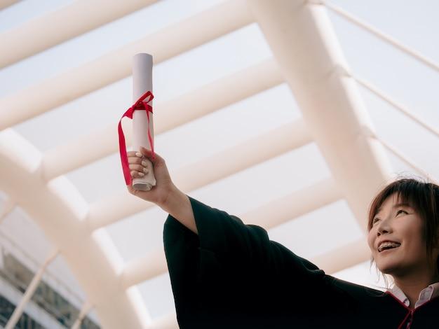 A menina em vestidos pretos guarda o certificado do diploma com feliz graduado.