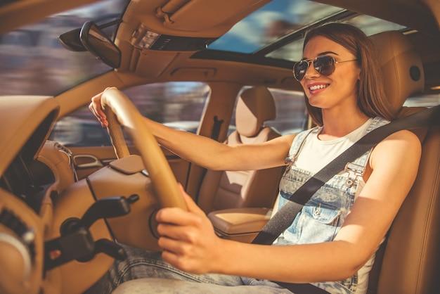 A menina em vidros de sol está sorrindo ao conduzir o carro.