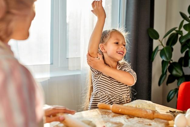 A menina embrulha as mangas antes de cozinhar, vai rolar a massa na cozinha
