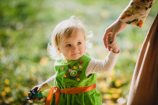 A menina encantadora com a mãe andando ao longo do parque