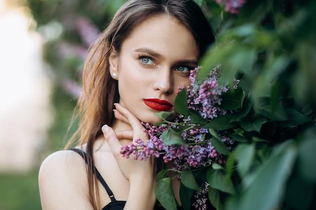 A menina encantadora fica perto de arbustos com flores