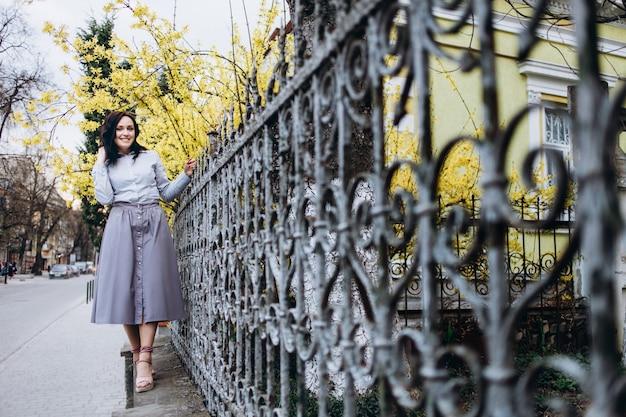 A menina encantadora fica perto do portão