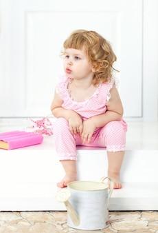 A menina encaracolado em um vestido cor-de-rosa senta-se com olhar pensativo e olha-se na distância