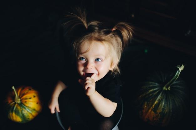 A menina enfiou em uma tigela com abóboras em torno e boca aberta