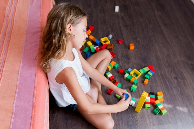A menina engraçada bonito do pré-adolescente que joga com brinquedo da construção obstrui a construção de uma torre em casa. crianças brincando. crianças na creche. criança e brinquedos. estilo de vida familiar