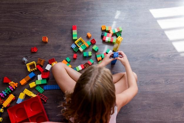 A menina engraçada bonito do pré-adolescente que joga com brinquedo da construção obstrui a construção de uma torre em casa. crianças brincando. crianças na creche. criança e brinquedos.