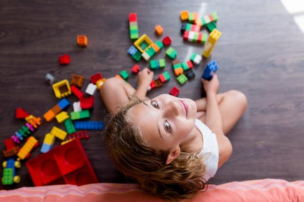 A menina engraçada bonito do pré-adolescente que joga com brinquedo da construção obstrui a construção de uma torre em casa. crianças brincando.