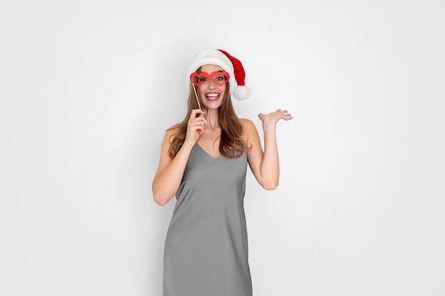 A menina engraçada do papai noel que ri usa óculos de coração de mentira, isolados no fundo branco, festa de ano novo