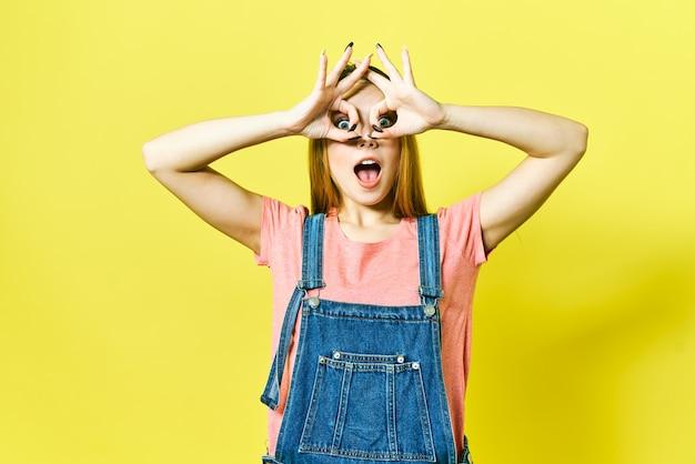 A menina engraçada e alegre mostra o sinal aprovado e piscadelas olhando a câmera isolada em fundo amarelo.