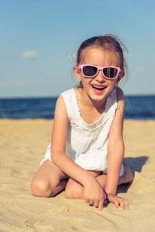A menina engraçada em vidros de sol está olhando a câmera.