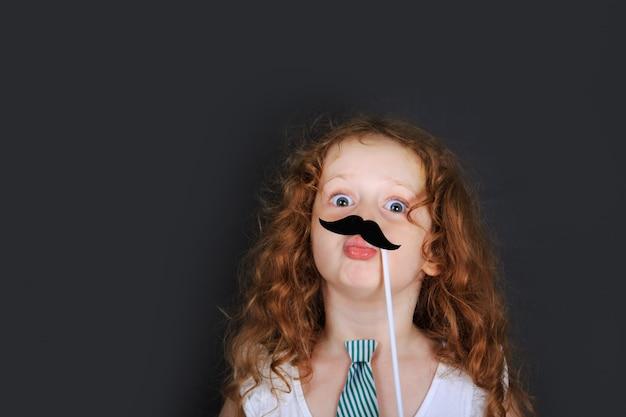 A menina engraçada prende o bigode do carnaval e manda beijos do ar.