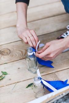 A menina entrega as flores tocantes em um vaso pequeno. Flores na garrafa.