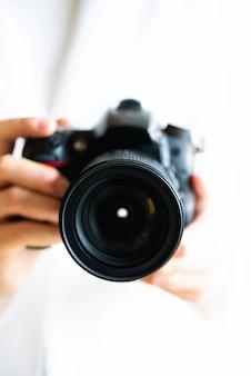 A menina entrega guardar a câmera da foto, fundo branco, espaço da cópia. viajar e atirar conceito