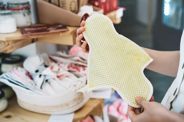 A menina escolhe absorventes menstruais de pano em uma loja de plástico grátis. um absorvente feminino ecológico reutilizável
