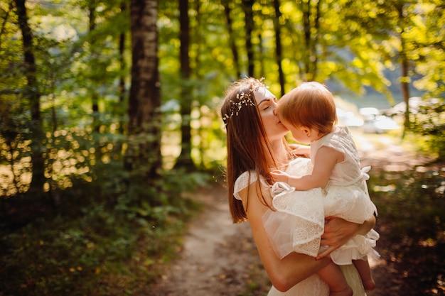 A menina esconde o rosto sentado nos braços da mãe