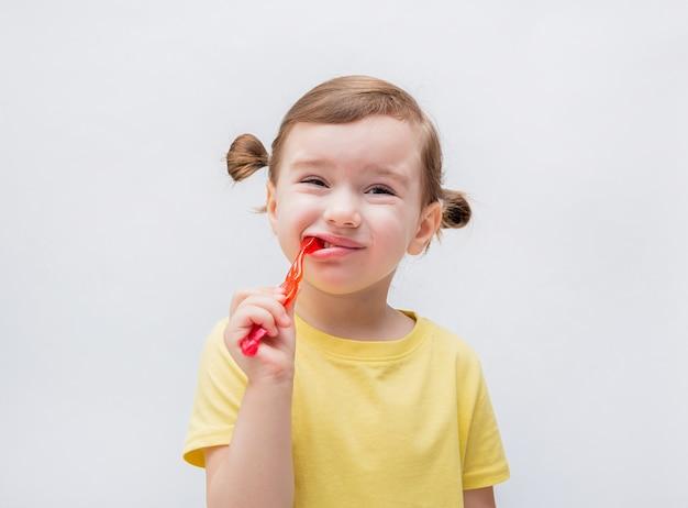 A menina escova os dentes com uma escova de dentes. cárie dentária. é um problema com os dentes. dor de dente.