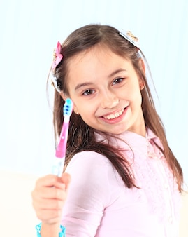 A menina escovando os dentes.