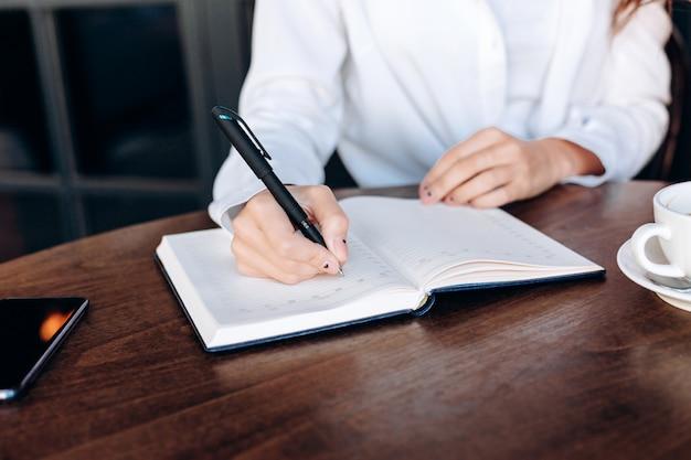 A menina escreve em um caderno em um café
