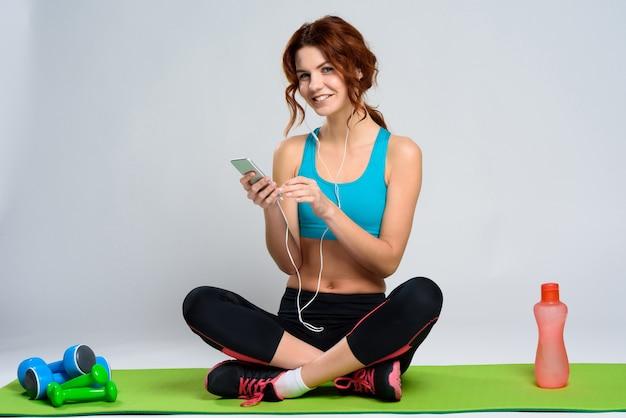 A menina escuta música com os auscultadores no tapete do gym.