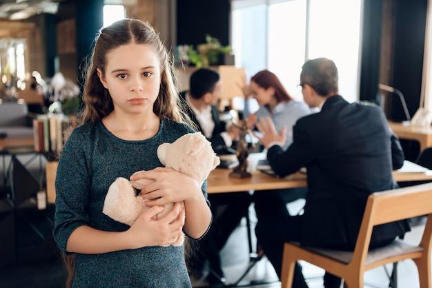 A menina está abraçando o urso de peluche no escritório do advogado da família.