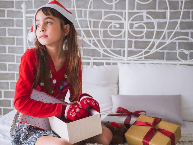 A menina está abrindo a caixa de presente no dia de natal