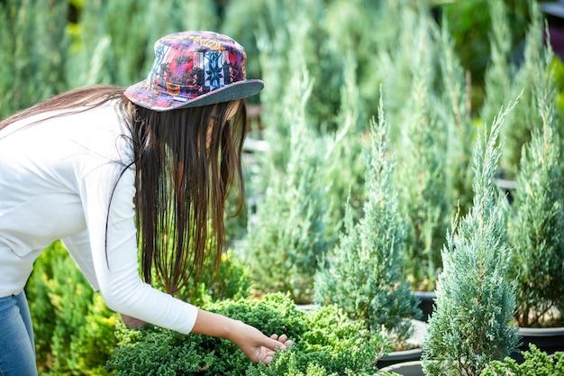 A menina está admirando as flores no jardim.