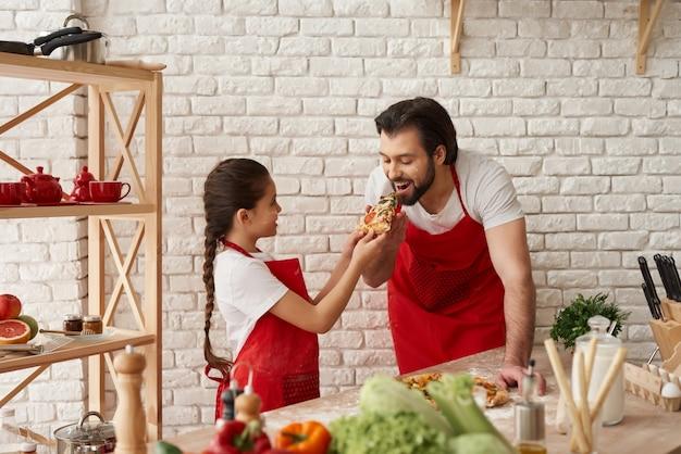 A menina está alimentando o pai com fome com uma fatia de pizza.