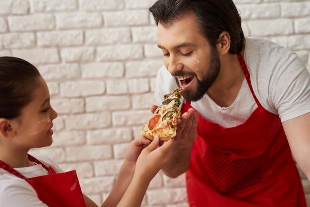 A menina está alimentando o pai com uma fatia de pizza.