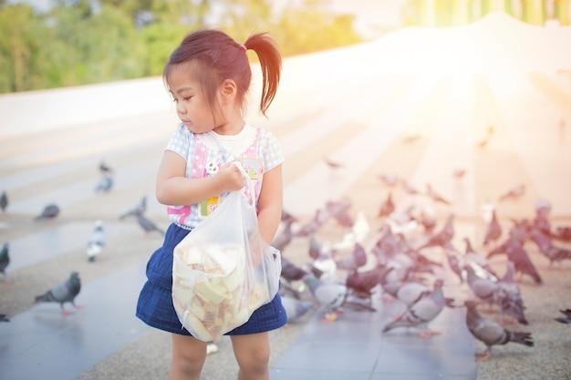 A menina está alimentando o retrato do pássaro