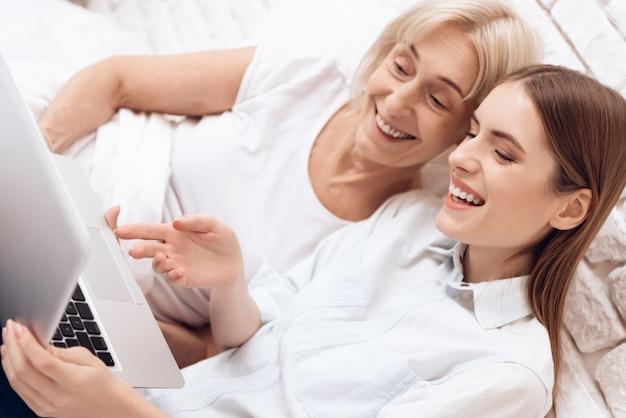 A menina está amamentando a mulher idosa na cama em casa com computador.