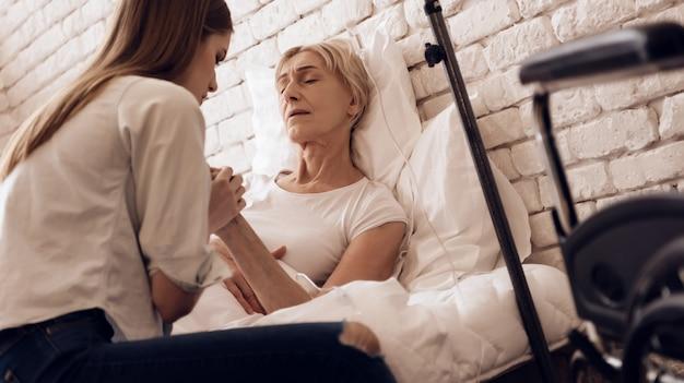A menina está amamentando a mulher idosa na cama em casa