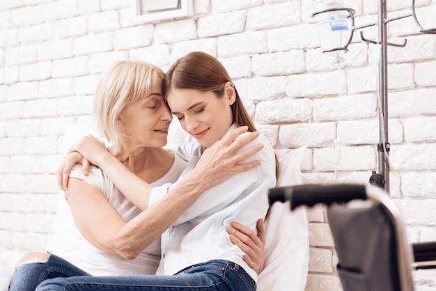A menina está amamentando a mulher idosa na cama na clínica