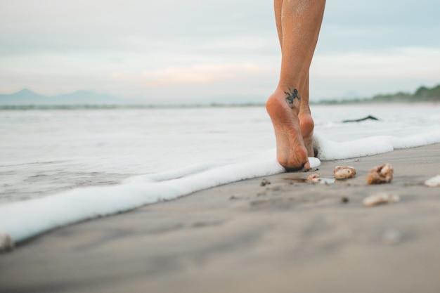 A menina está andando na praia