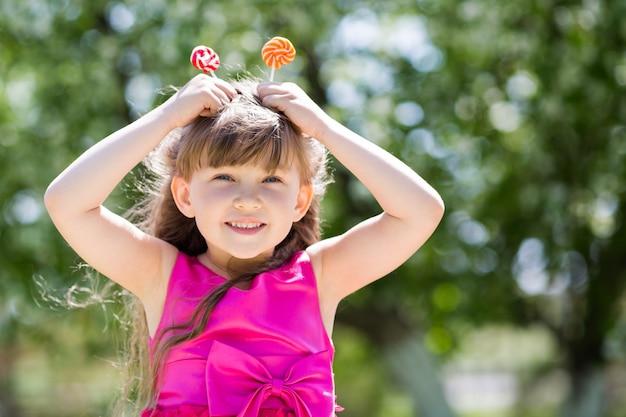 A menina está brincando com grandes doces no palito.