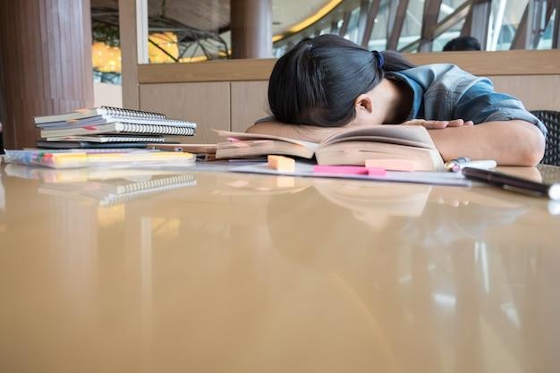A menina está cansada de ler livros, decidiu relaxar com a cabeça apoiada nos livros