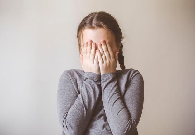 A menina está chorando cobrindo os olhos com as mãos.
