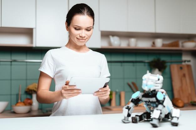 A menina está de pé na cozinha e segurando um tablet.