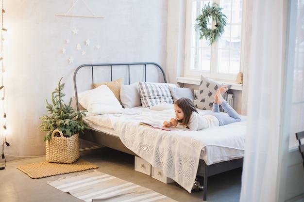 A menina está deitada no sofá e lendo um livro, a sala está decorada para o natal