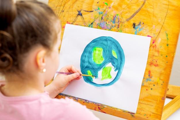 A menina está desenhando a terra por aquarelas em papel branco em um cavalete de madeira. conceito do dia da terra.
