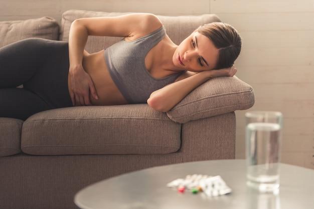 A menina está doente com anorexia deitada no sofá.