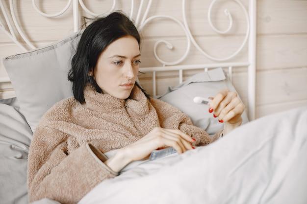 A menina está doente em casa, deitada na cama.