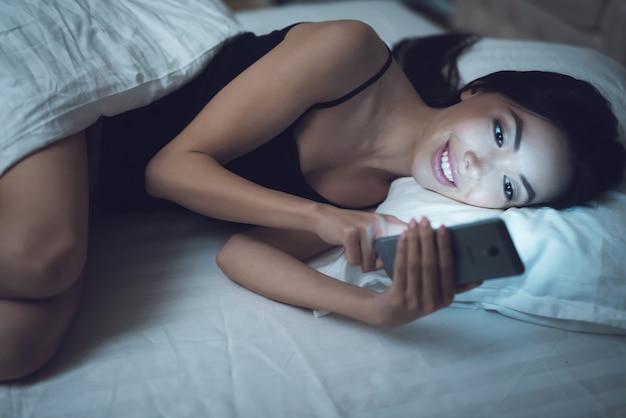 A menina está em um quarto escuro na cama olha o smartphone.