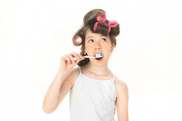 A menina está escovando os dentes.