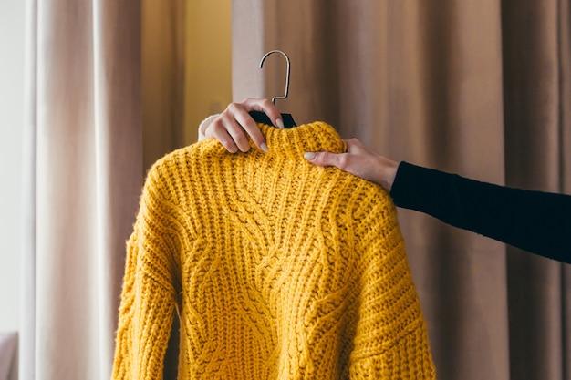 A menina está experimentando roupas na loja, perto do provador
